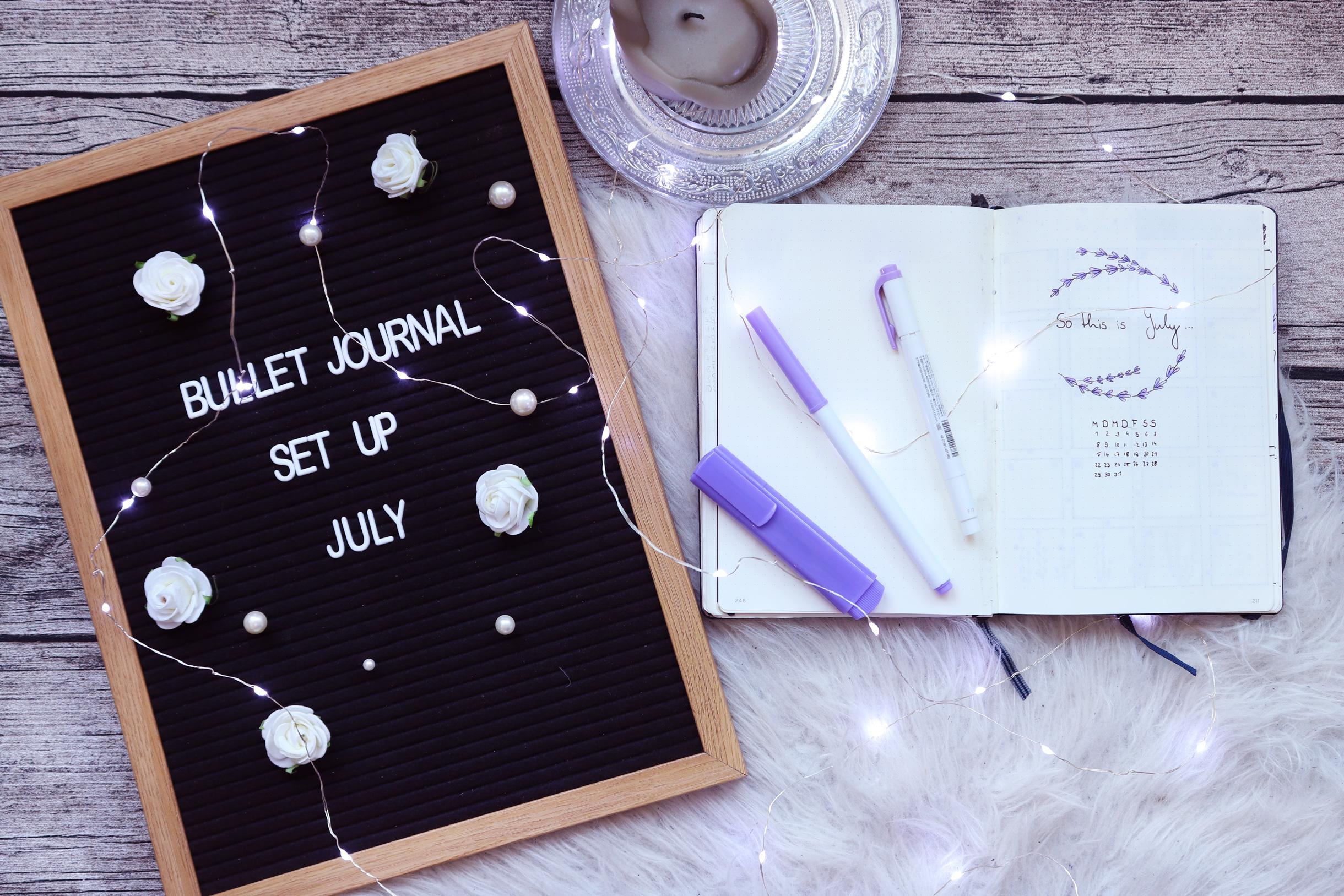Titelbild des Blogposts, Bullet Journal Set Up Juli mit Titelseite Juli und Journal, Lila stiften